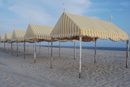 yellow striped tents on sandy ocean shoreline photo