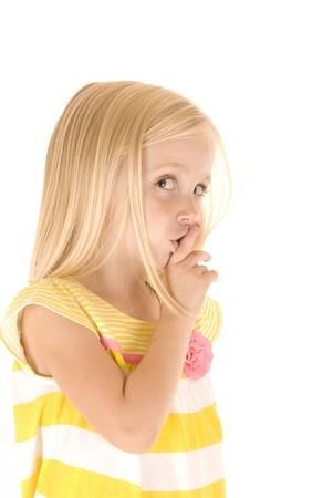 shushing: blonde girl shushing finger to lips