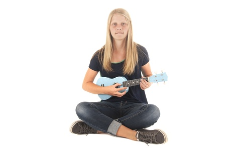 teenage girl sitting playing light blue ukulele Stock Photo