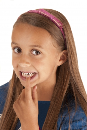 grinning: girl pointing at missing tooth pink headband Stock Photo