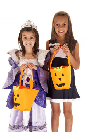 trick or treating: Halloween sisters princess cheerleader trick or treating  Stock Photo