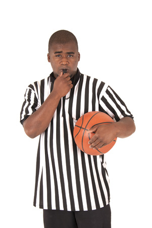 black referee blowing whistle holding a basketball Stock Photo