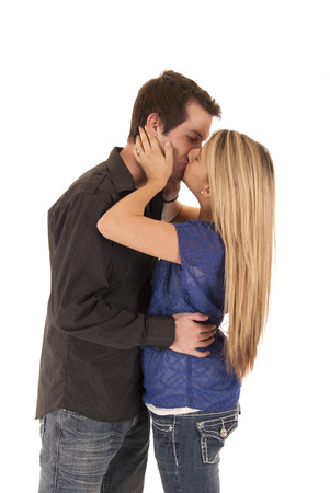 young couple enbracing kissing standing up hugging photo