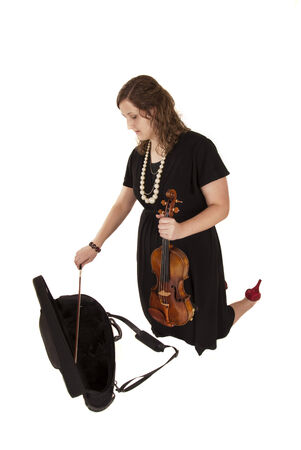 woman putting her violin away in case photo