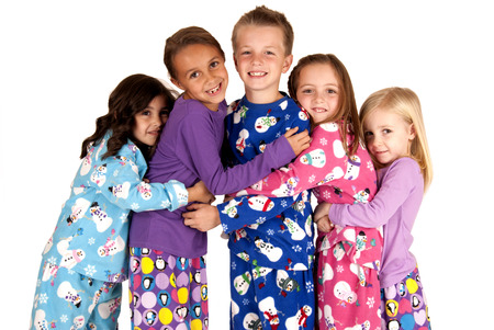 Children hugging in christmas holiday fleece pajamas
