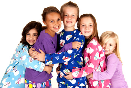 children in winter pajamas hugging each other photo