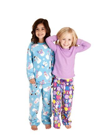 young girls standing wearing winter pajamas smiling photo