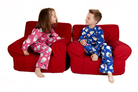 Two children laughing wearing winter pajamas sitting