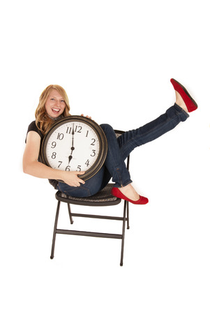 woman holding clock in chair with enthusiasm photo