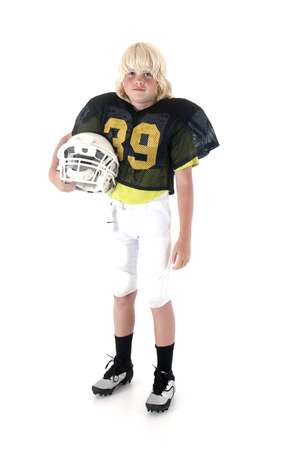Young American football player standing holding helmet
