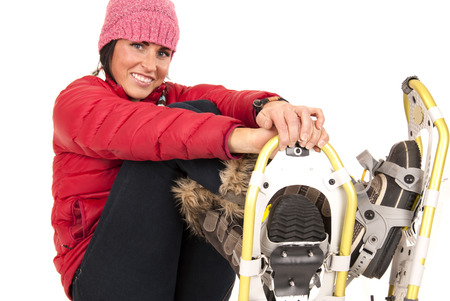 winter fashion: Smiling female model sitting in snow shoes