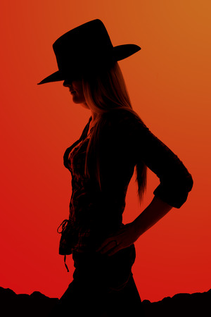 silhouette of cowgirl with hands on hips Stock Photo