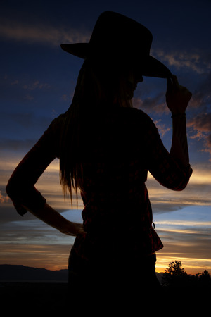 Silhouette of cowgirl tipping hat at sunset Stock Photo