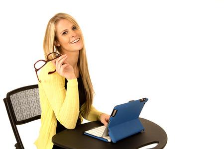 i pad: beautiful blonde holding glasses smiling at desk Stock Photo