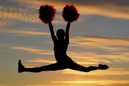 cheerleader silhouette leaping doing splits sunset background