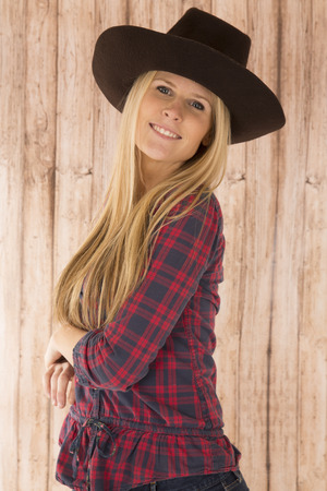 barnwood: Portrait of attractive cowgirl with barnwood background