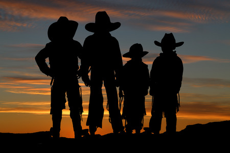 Silhouette of four young cowboys sunset background photo