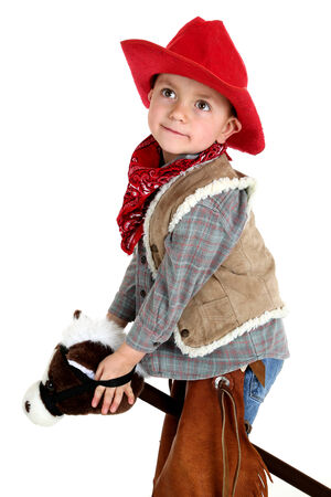 cute young cowboy riding stick horse playing photo