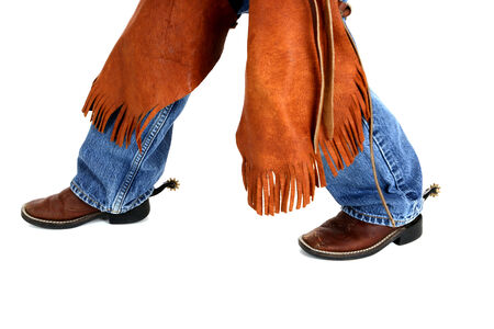 legs of  cowboy wearing chaps and boots Stock Photo