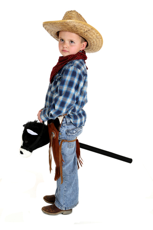 adorable young cowboy riding a stick horse photo