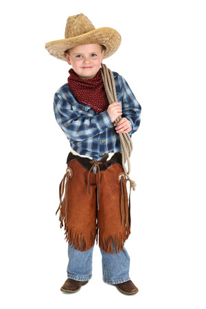 Cute young cowboy standing holding a rope Stock Photo
