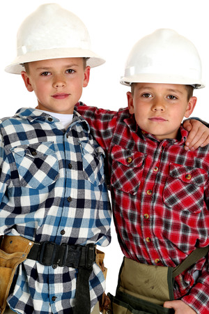 Two young brothers wearing hardhats hugging  photo