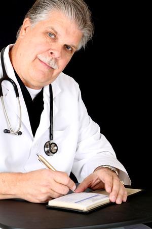 Handsome mature medical doctor writing a prescription photo