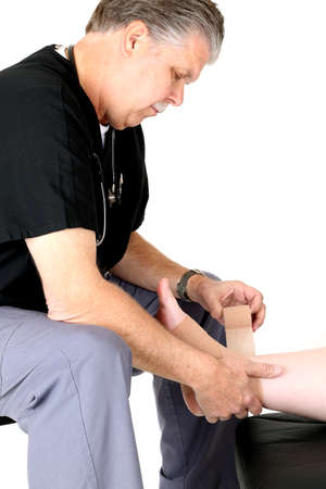 pediatrist: mature medical doctor wearing scrubs wrapping ankle Stock Photo