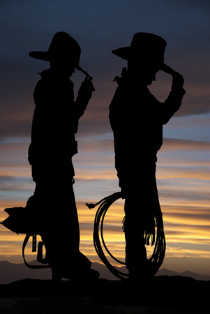 Silhouette of two cowboys standing sunset background  photo