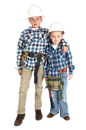 Brothers hugging standing wearing construction hard hats