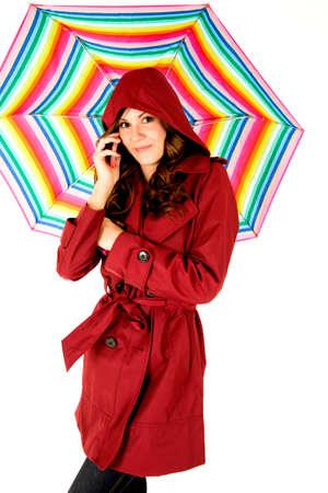rainbow umbrella: Female model on cellphone with rainbow umbrella