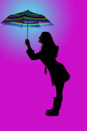 fun pose silhouette woman holidng colorful umbrella photo