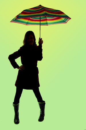 silhouette of woman holding umbrella green background photo