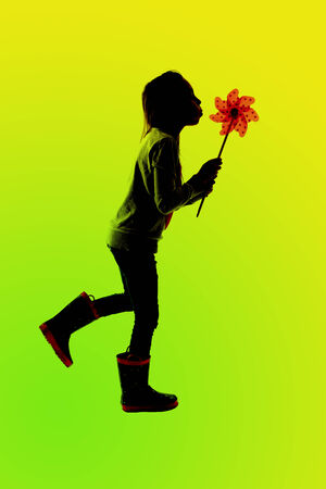 green silhouette of girl blowing toy pinwheel photo