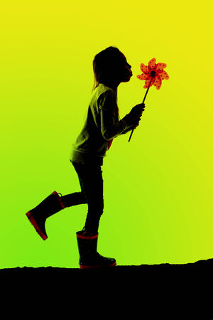 silhouette of girl walking blowing toy pinwheel photo