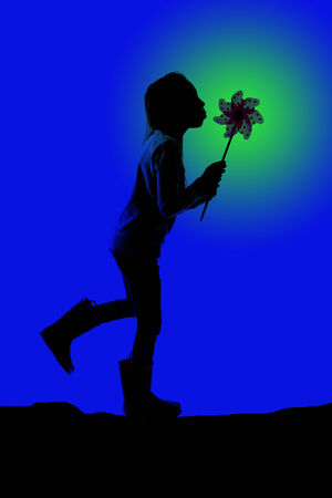 silhouette girl blowing toy pinwheel blue background photo