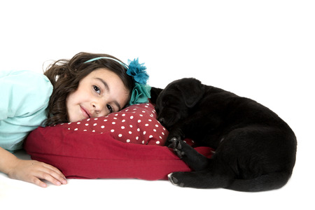 girl laying down by black puppy dog photo