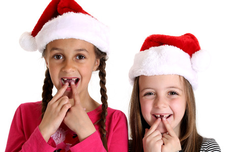 two girls wearing santa hats missing teeth