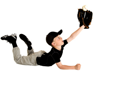 Young baseball player diving to catch ball
