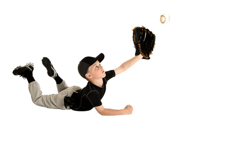 Young baseball player sliding to catch ball