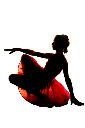 Silhouette of young ballerina balancing white background photo