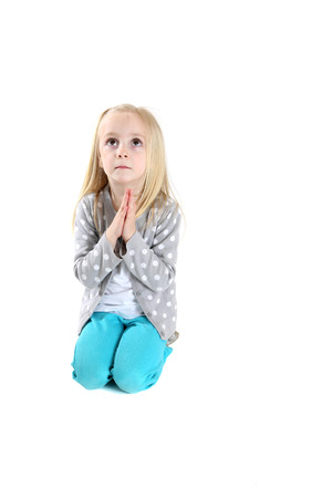 young girl kneeling in prayer looking up