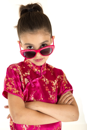 girl wearing chinese dress looking over sunglasses photo