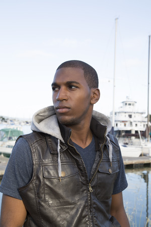 far off: black male looking far off at marina Stock Photo