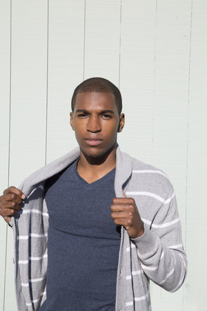 Attractive black male model holding striped sweater