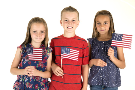 Three cute children holding American flags smiling