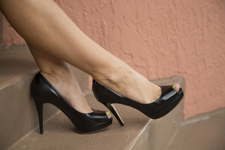 black heels: womans legs on stairs wearing black heels Stock Photo