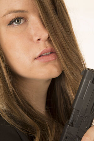 Close-up portrait woman holding pistol somber expression photo