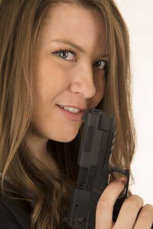 smirk: Close-up portrait woman holding pistol with smirk