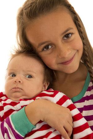 striped pajamas: Muchacha que sostiene el pijama de rayas hermana del beb� Foto de archivo